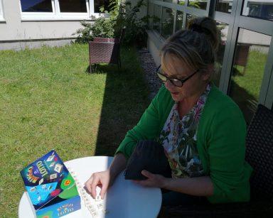 Ogród przed DPS. Terapeutka Beata Gadomska przy stoliku. Przed nią pudełko z grą Bingo.