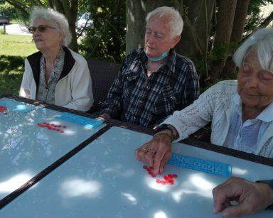 Seniorzy siedzą w cieniu drzew przy stoliku. Grają w Bingo.