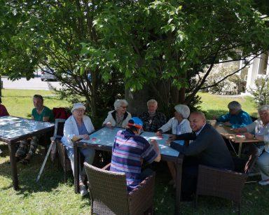 Seniorzy siedzą w cieniu drzew przy stolikach. Grają w Bingo.