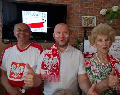 Sala. Kierownik Arkadiusz Wanat i dwoje seniorów. Na twarzach mają namalowane polskie flagi. Senior ma koszulkę z godłem Polski.