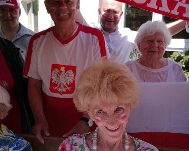 Ogród. Uśmiechnięci seniorzy. Na twarzach namalowali polskie flagi. Z tyłu kierownik Arkadiusz Wanat. Ma szalik z napisem Polska.