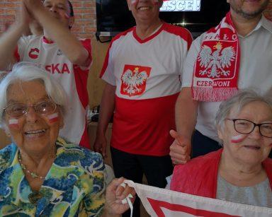 Sala. Kierownik Arkadiusz Wanat i seniorzy. Mają stroje kibiców. Na twarzach namalowali polskie flagi.