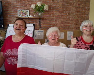 Trzy roześmiane seniorki. W rękach trzymają flagę Polski. Na twarzach mają namalowane polskie flagi.