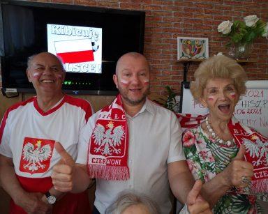 Sala. Kierownik Arkadiusz Wanat i seniorzy. Mają stroje kibiców. Na twarzach namalowali polskie flagi. Śmieją się.
