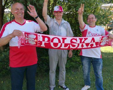 Ogród. Trzech seniorów trzyma szalik z napisem Polska. Na twarzach mają namalowane polskie flagi.