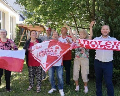 Ogród. Seniorzy i kierownik Arkadiusz Wanat. Mają stroje kibiców. Na twarzach namalowali polskie flagi.