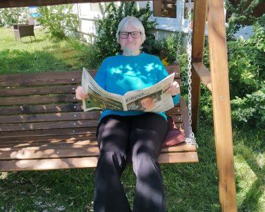 Seniorka siedzi w cieniu na ogrodowej huśtawce. W rękach trzyma rozłożona gazetę.
