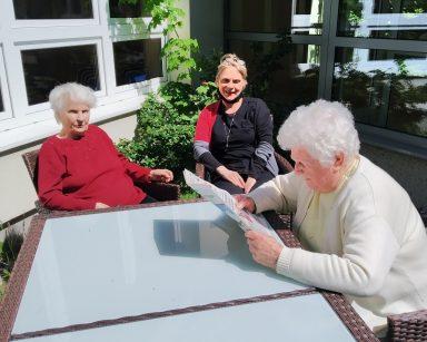 Trawnik przed budynkiem DPS. Dwie seniorki i terapeutka Beata Gadomska siedzą przy stole. Jedna seniorka czyta gazetę.