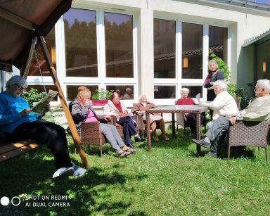 Trawnik przed DPS. Seniorzy siedzą w rattanowych fotelach, na drewnianej huśtawce. Czytają prasę, odpoczywają na słońcu.