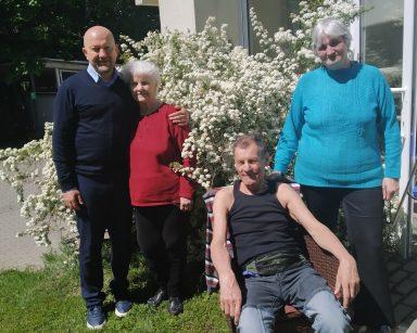 Troje seniorów i kierownik Arkadiusz Wanat na trawie. Za nimi kwitnący krzew i budynek DPS.