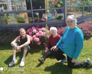 Troje seniorów i kierownik na trawie. Uśmiechają się i mrużą oczy od słońca. Za nimi kwiaty, wrzosy i ogród zimowy DPS.