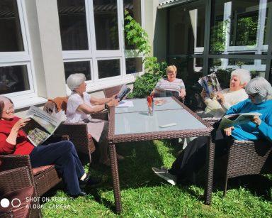 Trawnik przed DPS. Seniorki siedzą w rattanowych fotelach. Czytają prasę i odpoczywają na słońcu.