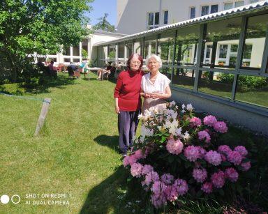Dwie seniorki przy różowych kwiatach. Za nimi inni seniorzy odpoczywają na świeżym powietrzu.
