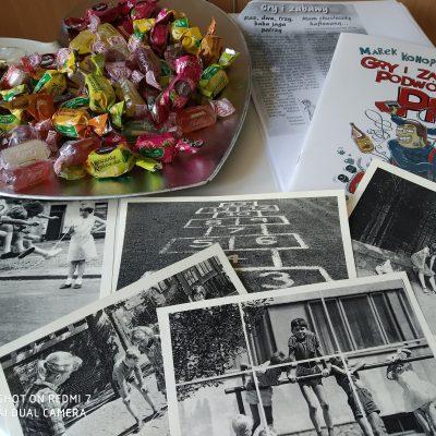 Srebrna taca z cukierkami. Obok czarno-białe pocztówki z grami i zabawami podwórkowymi oraz książki o grach.
