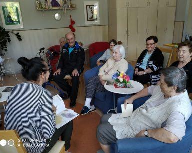 Terapeutka Magdalena Poraj-Górska zaczyna spotkanie. Przed nią siedzą uśmiechnięci seniorzy.