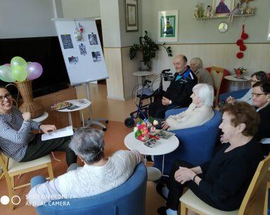Terapeutka Magdalena-Poraj Górska i seniorzy rozmawiają podczas spotkania. Wszyscy są uśmiechnięci.