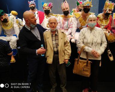 Sala teatru. Kierownik Arkadiusz Wanat i uczestnicy Dziennego Domu pozują do zdjęć z aktorami w kolorowych kostiumach.