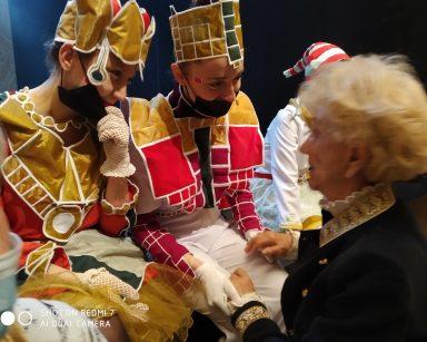 Sala teatru. Seniorka rozmawia z dwoma aktorkami w kolorowych kostiumach.