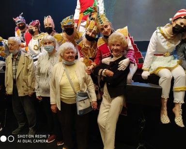 Sala teatru. W pierwszym rzędzie stoją seniorzy. Za nimi na scenie siedzą aktorzy w kolorowych kostiumach.