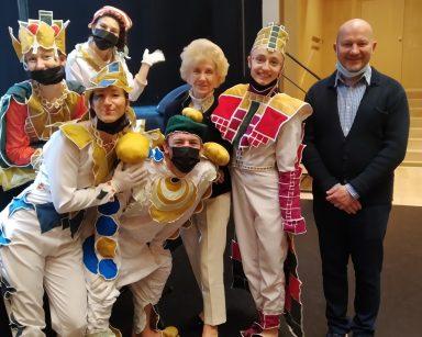 Sala teatru. Kierownik Arkadiusz Wanat, seniorka i aktorzy w kolorowych kostiumach stoją koło siebie uśmiechnięci.