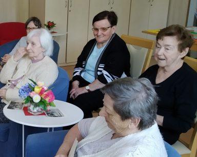Jasny pokój. Roześmiane seniorki siedzą obok siebie.