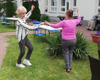 Patio przed DPS. Dwie seniorki tańczą na trawniku. Za nimi rozstawione stoły.