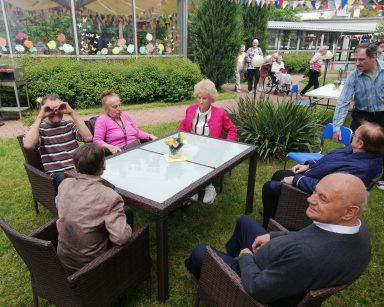 Patio przed DPS udekorowane trójkątnymi chorągiewkami. Seniorzy schodzą się na grilla. Część już siedzi przy stolikach.