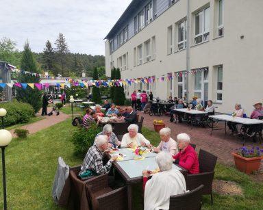Patio przed DPS udekorowane trójkątnymi chorągiewkami. Seniorzy i pracownicy siedzą przy stolikach, rozmawiają.