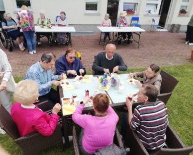 Seniorzy siedzą przy stolikach na patio przed DPS. Jedzą kiełbaski z grilla.