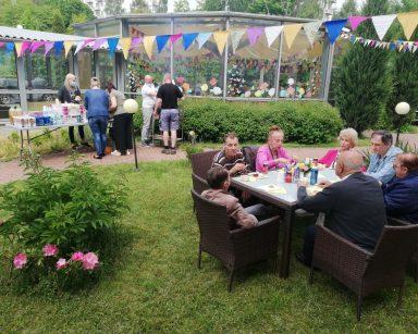 Seniorzy siedzą przy stolikach na patio przed DPS. Jedzą kiełbaski z grilla. W tle gród zimowy i pracownicy przy grillu.