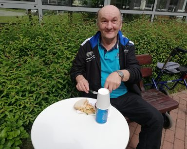 Uśmiechnięty senior siedzi przy stoliku na patio przed DPS. Kroi kiełbaskę z grilla.