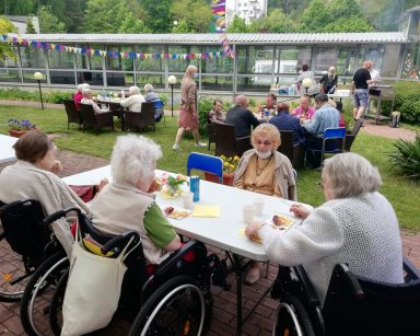 Seniorzy i pracownicy na patio przed DPS. Jedzą kiełbaski z grilla, rozmawiają. W tle gród zimowy i pracownicy przy grillu.
