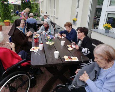 Seniorzy i pracownicy na patio przed DPS. Jedzą kiełbaski z grilla i rozmawiają.