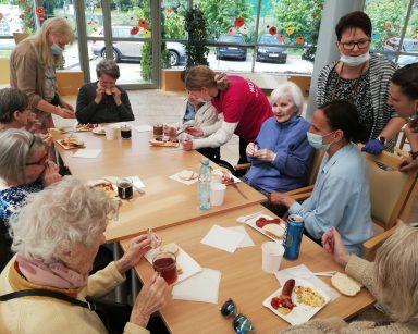 Ogród zimowy. Przy stołach seniorzy, wolontariusze i pracownicy, jedzą kiełbaski z grilla, rozmawiają.