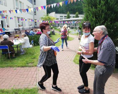 Patio przed DPS. Seniorzy, pracownicy i wolontariusze jedzą kiełbaski z grilla, rozmawiają, tańczą.