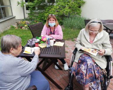 Na patio przy stoliku kierowniczka Ewa Siłakiewicz-Witt i dwie seniorki.