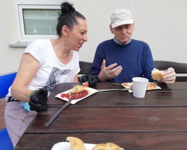 Terapeutka Magdalena Poraj-Górska i senior rozmawiają przy stoliku. Przed nimi tacki z grillowaną kiełbasą.