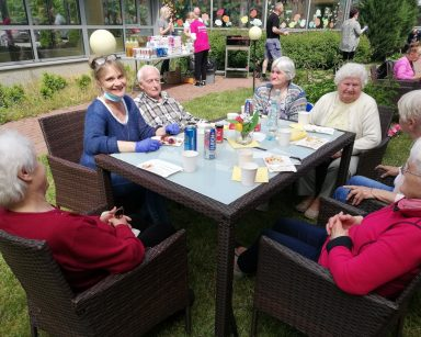 Patio przed DPS. Seniorzy, pracownicy i wolontariusze jedzą kiełbaski z grilla, rozmawiają.