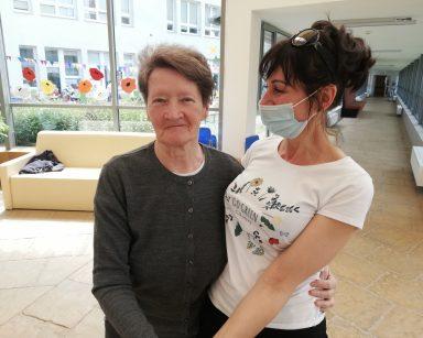 Przeszklony gród zimowy. Terapeutka Anna Rzepczyńska i seniorka stoją objęte i uśmiechają się do siebie.