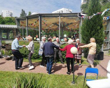 Patio przed DPS. Seniorzy tańczą w parach i większych grupach. W tle ogród zimowy.