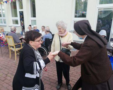 Na brukowanym patio tańczą razem siostra zakonna i dwie seniorki. W tle seniorzy i pracownicy przy stolikach.