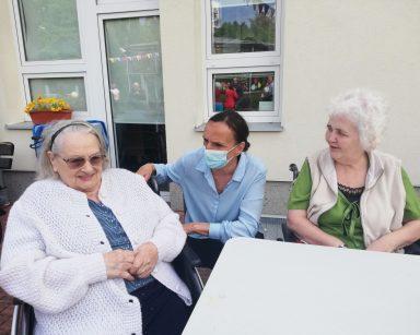 Dwie seniorki i wolontariuszka rozmawiają przy stole. W tle budynek DPS.