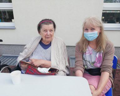 Seniorka i terapeutka Ewa Rodziewicz siedzą uśmiechnięte przy stole. W tle budynek DPS.