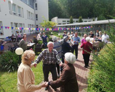 Patio przed DPS. Seniorzy tańczą, rozmawiają, siedzą przy stolikach.