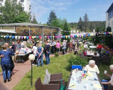 Patio przed DPS. Seniorzy, pracownicy, wolontariusze tańczą, rozmawiają, jedzą przy stolikach.