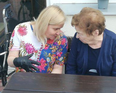 Neurologopedka Anna Szmaja-Wysocka i seniorka rozmawiają przy stole. W tle budynek DPS.