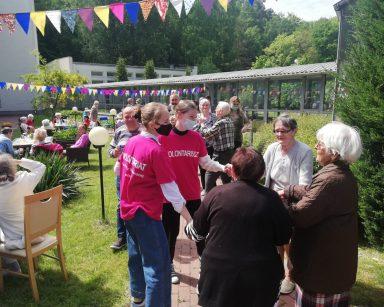 Patio przed DPS. Seniorzy, pracownicy, wolontariusze siedzą przy stolikach, tańczą, rozmawiają.
