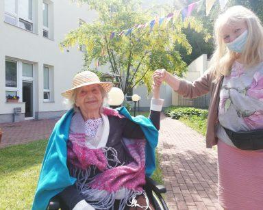 Terapeutka ewa Rodziewicz i seniorka trzymają się za ręce. W tle budynek DPS i kolorowe chorągiewki.