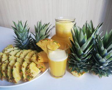 Na blacie zielone pióropusze ananasów, pokrojony ananas na talerzu, obok dzbanek i szklanka soku z ananasa.