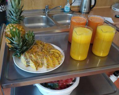 Metalowy wózek. Na nim ananas, talerz z plastrami ananasów i zielonym pióropuszem. Obok dzbanki z sokami.
